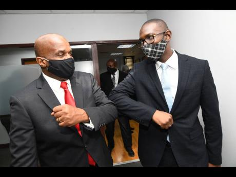 Greg Christie (left), executive director of the Integrity Commission, knocks elbows with Kevon Stephenson, director of investigations, on Christie's first day on the job. Christie, a former contractor general who was criticised for his zealotry in fighti