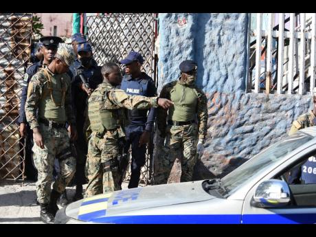 Members of the Jamaica Defence Force and the Jamaica Constabulary Force search a building along Fourth Street in Greenwich Town, Kingston, on Thursday. The community has been declared a zone of special operations from July 1 to July 14, 2020.