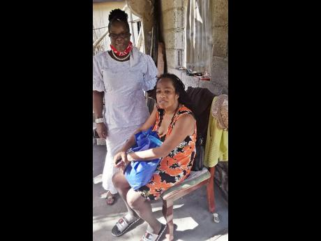 Minister Claudia Howard (left) of Love and Faith World Outreach Ministry in Port Maria, St Mary, presents a package to Audrey Sterling who lost all her possessions in a recent fire.