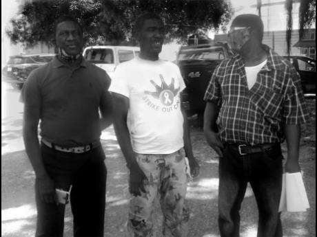 Mentally challenged farmer of St Elizabeth, Abraham Lawrence (second left) and his brothers outside the Black River Parish Court yesterday, where he was offered $10,000 bail.