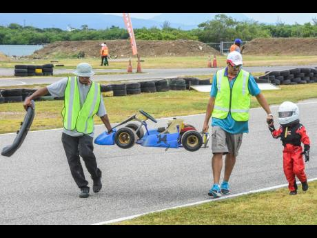 Marshals recovering a disabled kiddie kart and karter after a race.