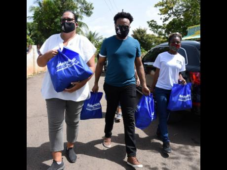 From left: Saffrey Brown, project manager of Private Sector Organisation of Jamaica (PSOJ) COVID-19 Jamaica Relief Fund; Kalando Wilmoth, communication specialist; and Annette Thompson walk with care packages in Wakefield, Linstead, St Catherine, to delive