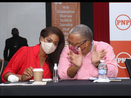 People's National Party President Dr Peter Phillips in dialogue with Lisa Hanna, chief campaign spokesperson, at a meeting of Regions One and Six councillors and councillor caretakers at the S Hotel in Montego Bay, St James, on Sunday.