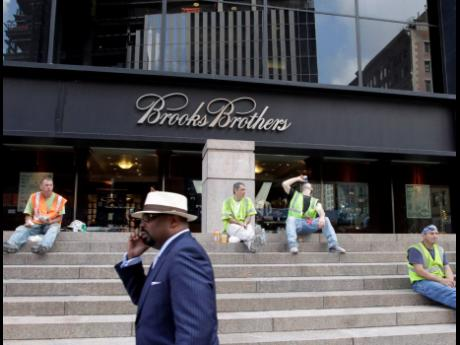 In this August 4, 2011 photo, a man passes a Brooks Brothers store on Church Street in New York's financial district.