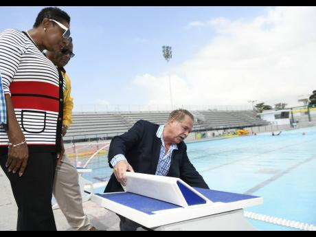 Martin Lyn (right), president, Aquatic Sports Association of Jamaica, explains the technologies involved in the starting blocks to Minister of Sport Olivia Grange (left) and Major Desmon Brown, general manager, Independence Park Limited, during the present