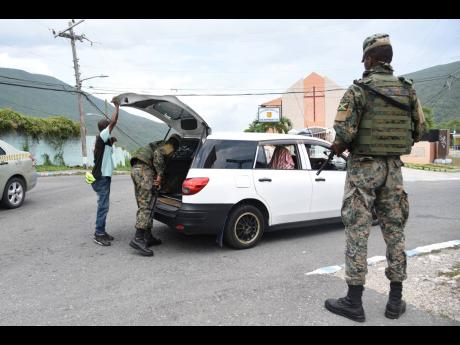 Members of the security forces conduct a search of a vehicle at a checkpoint in August Town, St Andrew, yesterday as a zone of special operation went into effect in the area.