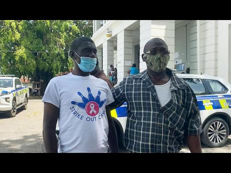 Mentally challenged farmer of St Elizabeth Abraham Lawrence (left) and his brother, Llewellyn, leave the Santa Cruz Parish Court yesterday. Abraham was freed after spending more than 25 years behind bars without being tried for alleged offences he committe