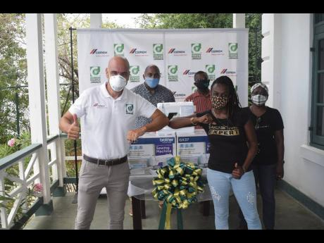 Yogo Castro (left), general manager at Carib Cement Company Limited, elbow bumps dressmaker Roselyn Logan following the handing over of sewing machines to members of three community groups from the Bull Bay, Rockfort and Mountain View/Vineyard Town areas o