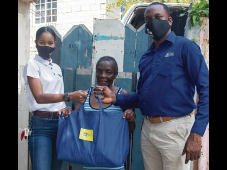 Betty Ffrench (centre) accepts her care package from Kimberly Atkinson (left), communication and client services manager, JN Small Business Loans, and Dane Baker, client relations manager, JNSBL Region 8. Ffrench was one of several elderly clients who rece