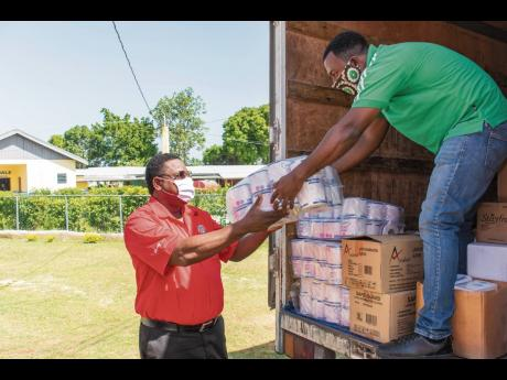 RUBiS Energy Jamaica Limited's Human Resource Manager Donnovan Dobson (left) helps to offload personal care items that were donated to the Santa Cruz Infirmary in St Elizabeth on July 2 as part of the organisation's efforts to assist in preventing the