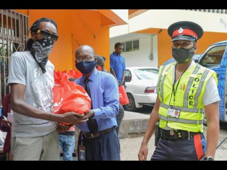 NCB's Gratitude Bus was on the move with the support of members of the Jamaica Constabulary Force. Here, NCB's Devon Wilson (centre) hands over a care package to a resident of the Mount James community in Stony Hill, St Andrew, during a recent visit to