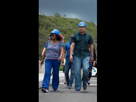Permanent Secretary Audrey Sewell walks alongside Prime Minister Andrew Holness during a tour of an overpass on Mandela Highway on Sunday, July 21, 2019.