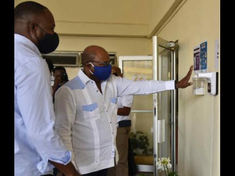 Minister of Tourism Edmund Bartlett (right) adheres to the protocols of a temperature check and hand sanitisation with automated equipment ahead of entering the reception area of the Golf View Hotel in Mandeville. At left is owner/director of Golf View Hot
