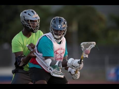 Raheem Pusey (right) goes on the offensive while being marked by Matthew McLeod during a Jamaica College lacrosse team training session at Jamaica College Ashenheim Stadium on Thursday January 16, 2020.