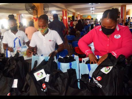 LASCO Financial Services Limited's Sponsorship and Promotions Officer, Nikeisha Alexander (right,) and LASCO Money brand ambassadors prepare donation packages filled with personal care and food items for Break Through PHD Ministries during a handover ses