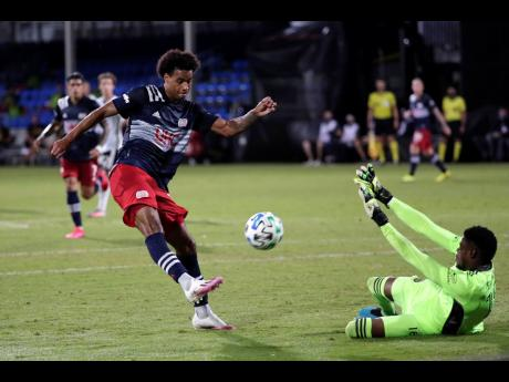 Philadelphia Union goalkeeper Andre Blake (right) makes a save as New England Revolution forward Tajon Buchanan shoots on goal during the first half of an MLS match in Kissimmee, Florida, on Saturday, July 25.