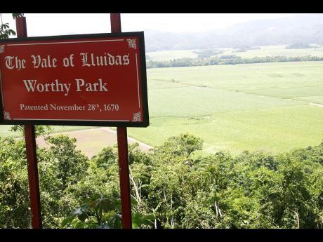 In this Gleaner file photo, the Worthy Park Estate canefields form the backdrop to a sign seen from the  Lluidas Vale main road in St Catherine.