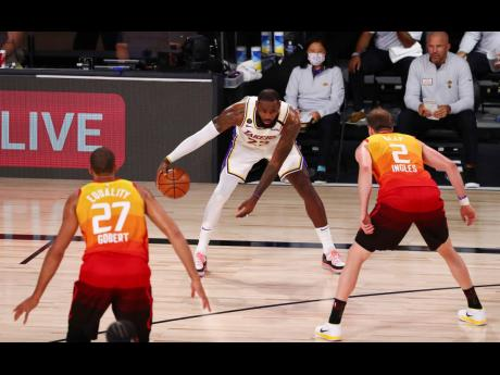 Los Angeles Lakers forward LeBron James (centre) is defended by Utah Jazz guard Joe Ingles (right) and centre Rudy Gobert during the first half of an NBA basketball game on Monday, August 3, in Lake Buena Vista, Florida.