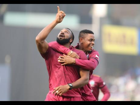 West Indies' white ball captain Kieron Pollard (left) celebrates the dismissal of India's captain Virat Kohli during the second one-day international cricket match between India and West Indies in Visakhapatnam, India, Wednesday, December 18, 2019.