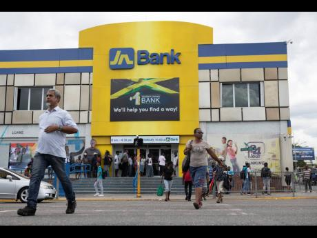 Persons walk by the JN Bank branch at Half-Way Tree, Kingston.