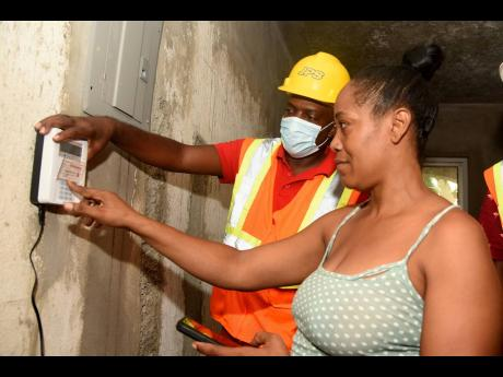 Yvette Burke Pearson, a resident of Standpipe, St Andrew, is instructed by Jamaica Public Service Company technician Sheldon Simms on the correct steps to take when inputting credit into the prepaid keypad on Tuesday. The community will, as at Friday, be t