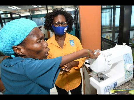 Daphne Williams (left) pronounces a blessing on her sewing machine after Claudette Christie, group marketing and communications manager of the Jamaica Co-operative Credit Union League, presented the donation in May Pen, Clarendon, on Wednesday. The 51-year
