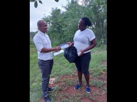 Cara Campbell-Ellis accepts a donation from Valdano Dunbar of the Jamaica Progressive Party.