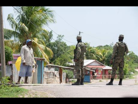 Members of the Jamaica Defence Force speak with a resident as he attempts to enter the quarantined zone in Sandy Bay, Clarendon, on Thursday, August 6. Residents of the community awoke to a 14-day COVID-19 lockdown.