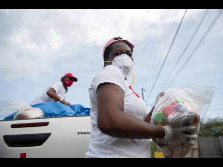 Members of the Jamaica Red Cross and Ministry of Labour and Social Security assisted with care packages and other logistics for residents throughout the community of Sandy Bay, Clarendon, on August 6, 2020, at the start of  the 14-day COVID-19 lockdown imp