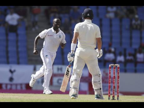 AP West Indies' Kemar Roach (left) celebrates after dismissing England's Rory Burns during day one of the second Test cricket match at the Sir Vivian Richards Stadium in North Sound, Antigua and Barbuda, on January 31, 2019.