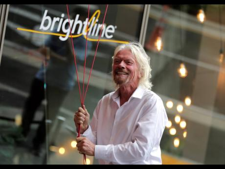 In this April 2019 photo, Richard Branson of Virgin Group prepares to unfurl a banner during a naming ceremony for the Brightline train station.
