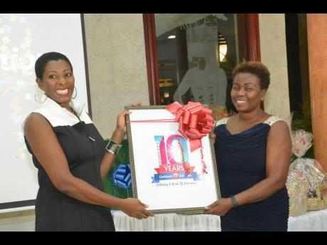 Debra Frazer (left), chief executive officer at Caribbean HR Solutions, presents Caribbean HR Solutions 10-year memento to Gloria Henry, president of the Global Services Association of Jamaica.