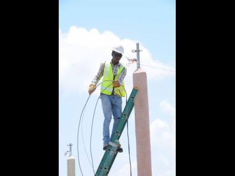 A JPS crewman installs power lines in Clarendon. Large consumers of electricity will soon be able to wheel power to satellite operations using the JPS network at rates that are still to be determined.