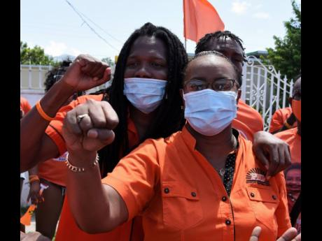 Damion Crawford, PNP vice-president, escorts Venesha Phillips, candidate for St Andrew Eastern, to the nomination centre at Mona High School on Tuesday, August 18.