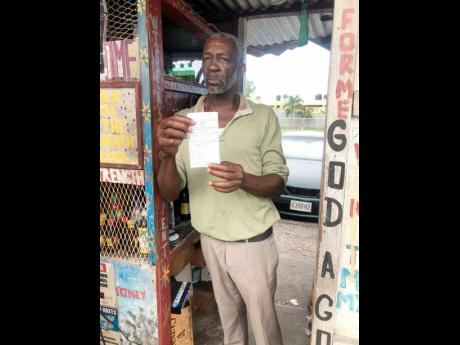 Everton 'Shut' Richards displays a copy of a receipt he received from the Constant Spring police after reporting at least three break-ins at his stall on Mannings Hill Road in St Andrew.