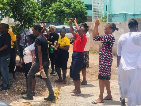 Members of City of Refuge Endtime Prophetic Ministries gather yesterday along Darling Street, Kingston.