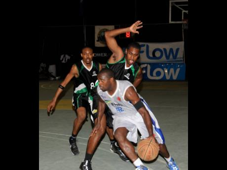 In this file photo from August 16, 2013, an Urban Knights player (front) is challenged by two Spanish Town Spartans opponents during Game Two of the FLOW National Basketball League finals at the National Stadium Court.