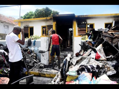 Orett Simpson (left) and Andrew White clearing the charred rubble from a house on Arthur Jones Avenue in St Andrew yesterday. The house was gutted by fire on Wednesday night.
