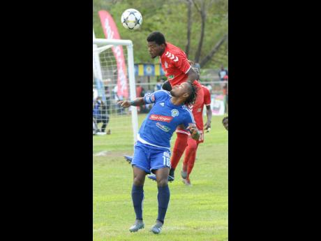 Mount Pleasant FA's Kemar Beckford (on ground) challenges UWI FC's Stephen Barnett for an aerial ball during a Red Stripe Premier League game at Drax Hall in St Ann on Sunday, March 31.