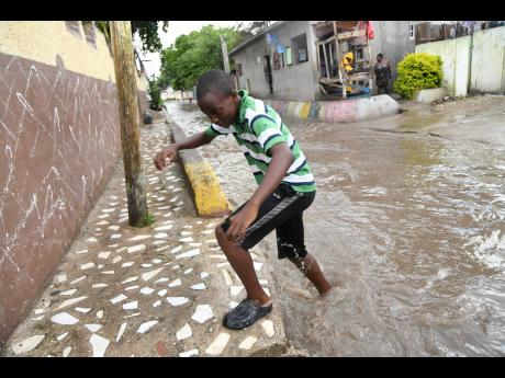 A boy crossing a section of the flooded White Lane yesterday in Waterhouse, St Andrew. The roadway looks like a part of the official drainage network whenever it rains in Waterhouse, St Andrew.