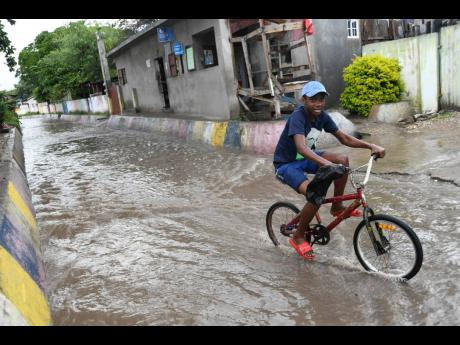 A boy rides through a flooded White Lane in Waterhouse, St Andrew, as water runs from Penwood Drive on to the lane after a shower of rain yesterday.