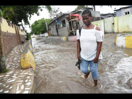 Beverley Jackson walks in the murky water to cross White Lane yesterday after it was inundated after a shower of rain.