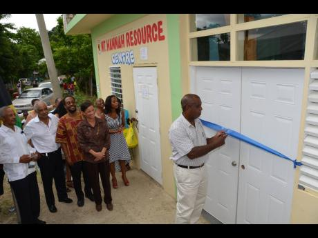 Hanover Eastern Member of Parliament Dr D.K. Duncan (second left) and other officials look on as community member John Whyte cuts the ribbon to signal the official opening of the Mount Hannah Resource Centre in Hanover, which was established at a cost of a