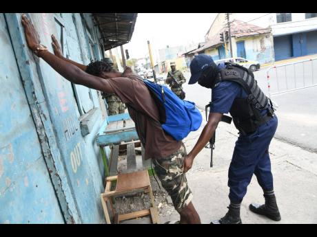 A cop searches a passer-by at a state of emergency checkpoint at North Street in central Kingston moments after Prime Minister Andrew Holness announced a 14-day crackdown in the Kingston Western and Central police divisions on Sunday, June 14.
