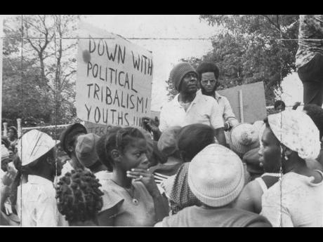 Dr D.K. Duncan (in glasses), general secretary of the People's National Party, speaking with a group of demonstrators at the gates of Jamaica House in this mid-1970s photo. The group from South West St Andrew visited Jamaica House, demanding to see Prim