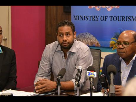 Kamal Bankay (left), chairman of the Carnival in Jamaica stakeholders committee, sitting alongside Edmund Bartlett, minister of tourism, at press conference COVID in March. ??