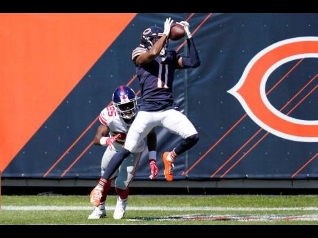 Chicago Bears wide receiver Darnell Mooney catches a 15-yard touchdown pass as New York Giants cornerback Corey Ballentine defends during the first half of an NFL football game in Chicago, Illinois, yesterday.