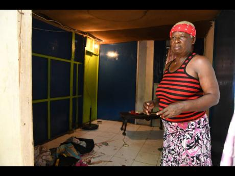 Patricia Shaw is a picture of pain as she stands in the room where her daughter, Nichola Pink, was shot dead in Denham Town, Kingston, on Sunday. Two others were slain in the Chestnut Lane gun attack.