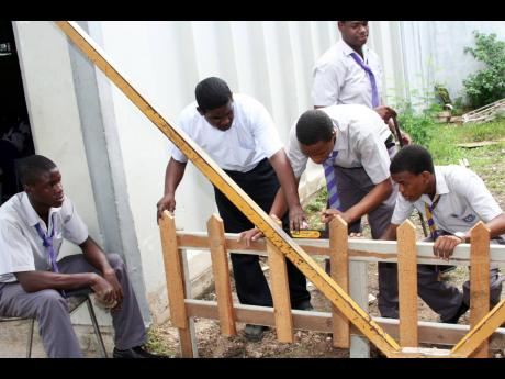 In this 2007 Gleaner photo, woodwork teacher Lloycent Gordon checks if a fence his students are working on is level during class at Ascot High School in Portmore, St Catherine.