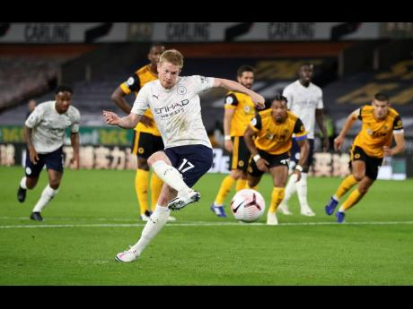 Manchester City's Kevin De Bruyne scores his team's first goal from the penalty spot during their English Premier League match against Wolverhampton Wanderers at Molineux Stadium in Wolverhampton, England, yesterday.